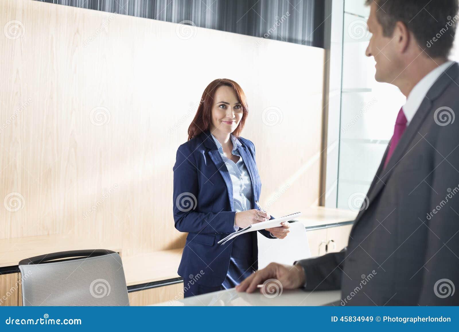 Homme d affaires parlant avec le réceptionniste dans le bureau