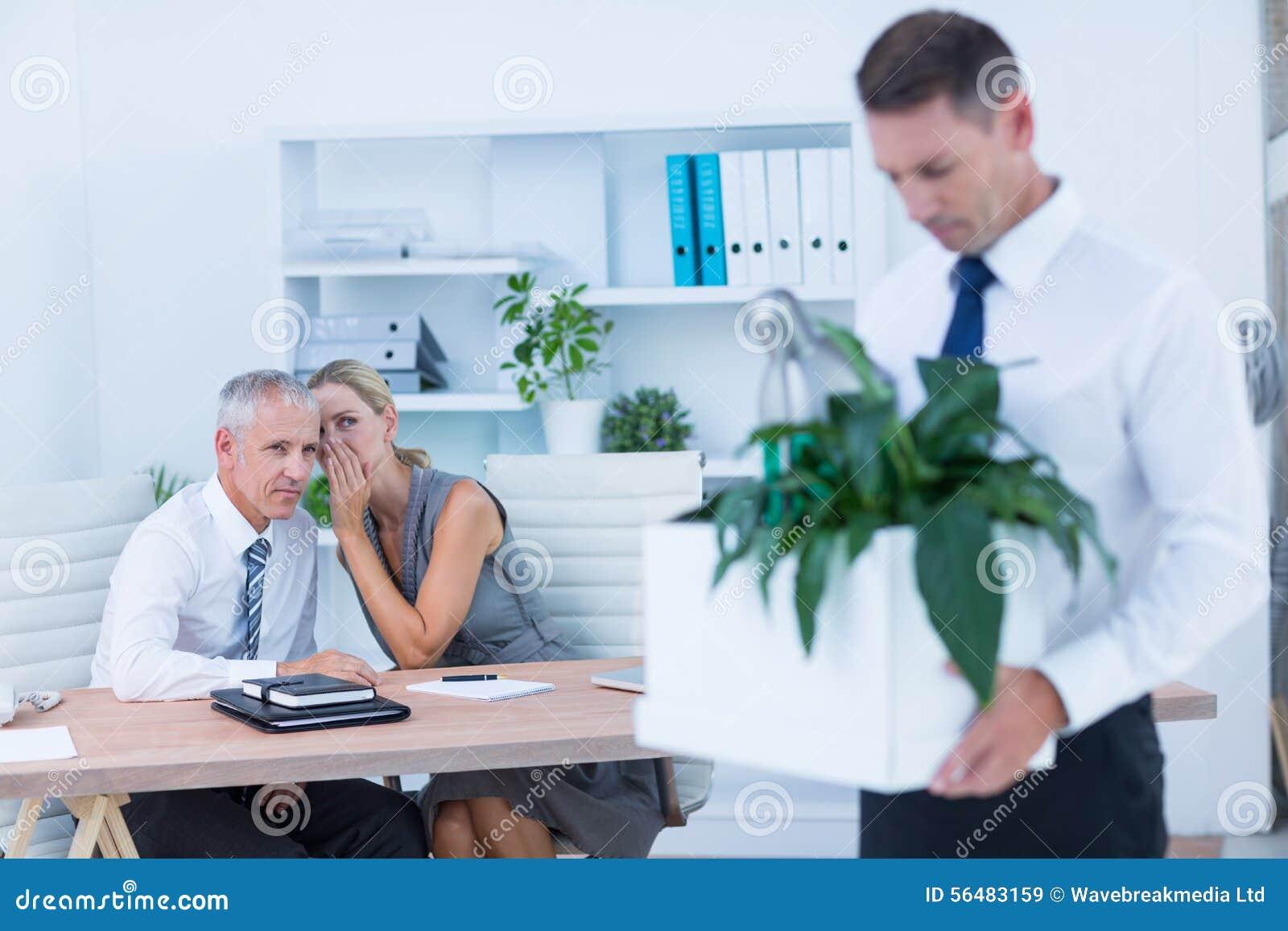 Homme d affaires portant ses affaires avec des collègues derrière