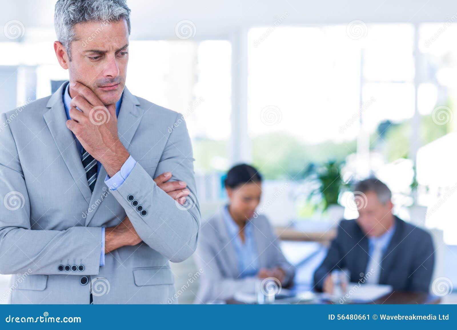 Homme d affaires réfléchi avec ses collègues derrière lui