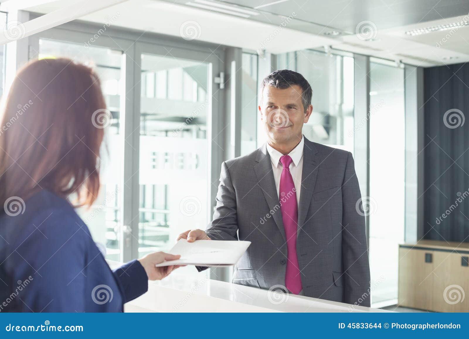 Homme daffaires recevant le document du réceptionniste dans le