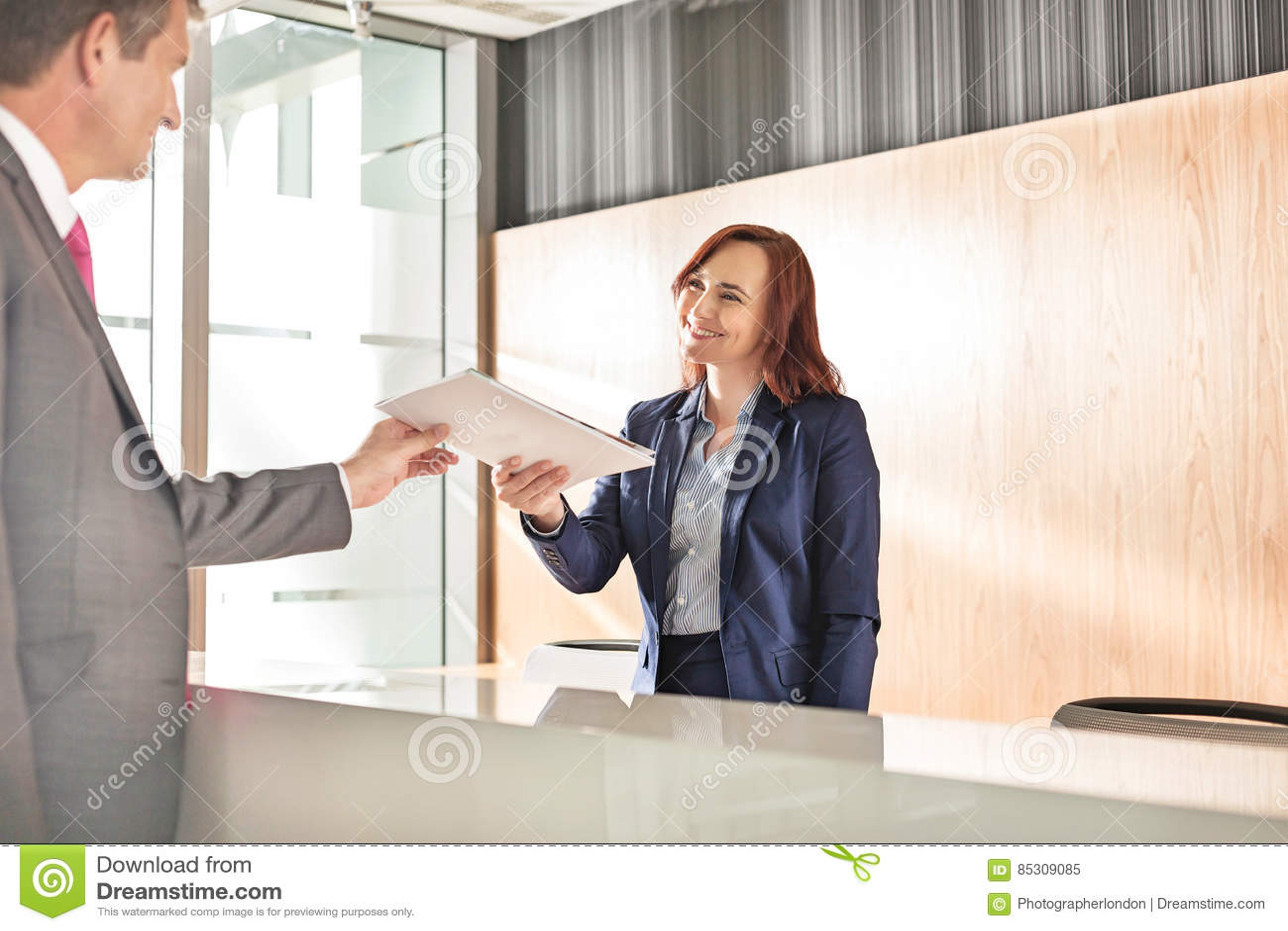 Homme d affaires recevant le document du réceptionniste dans