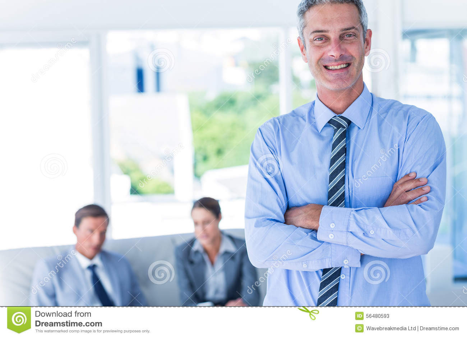 Homme d affaires regardant l appareil-photo avec ses collègues derrière lui