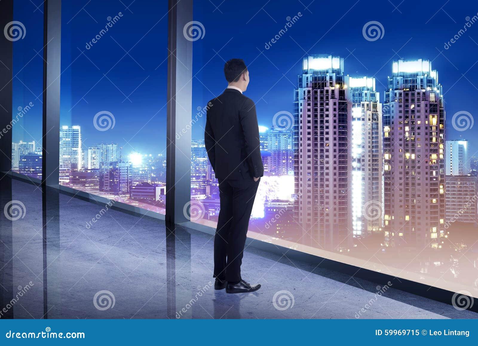 Homme daffaires regardant la ville de sa pièce de bureau image