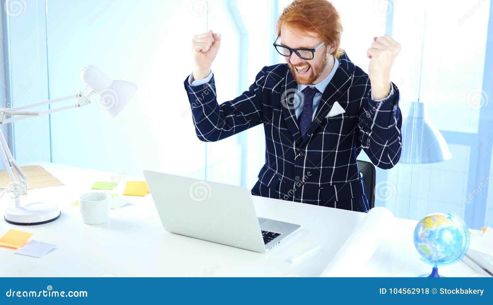 Homme d affaires roux Celebrating Success tout en travaillant sur l ordinateur portable, excitation