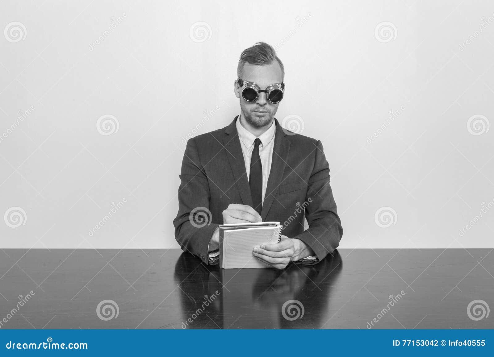 Homme d affaires s asseyant au bureau avec le bloc-notes