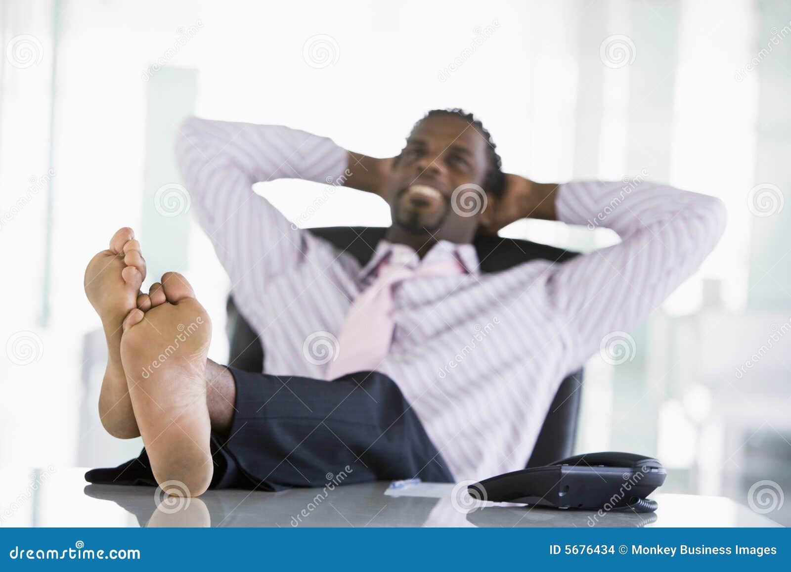 Homme d affaires s asseyant dans le bureau avec des pieds sur le