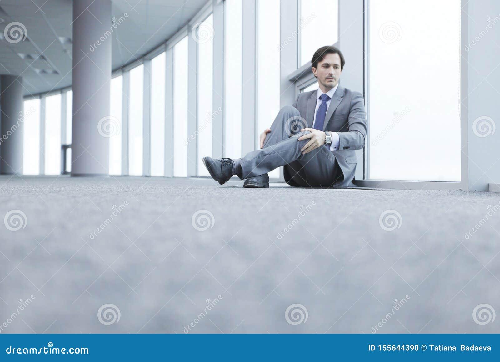 Homme d affaires s asseyant sur le plancher