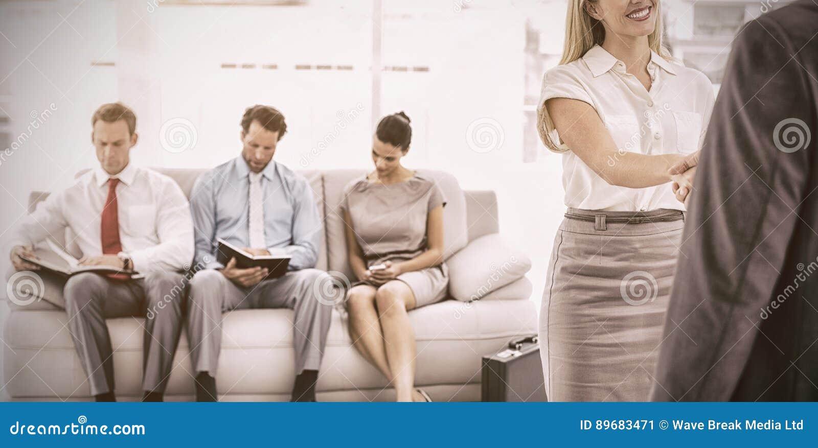 Homme d affaires serrant la main à la femme sans compter que l entrevue de attente de personnes