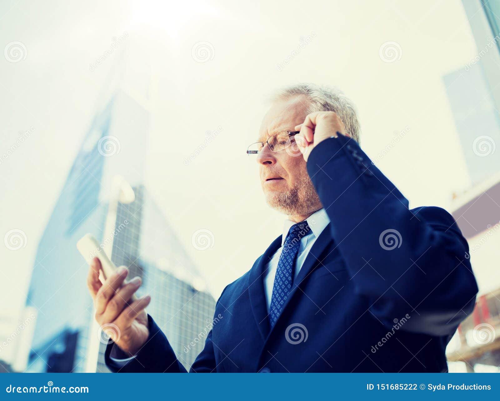 Homme d affaires sup?rieur avec le smartphone dans la ville