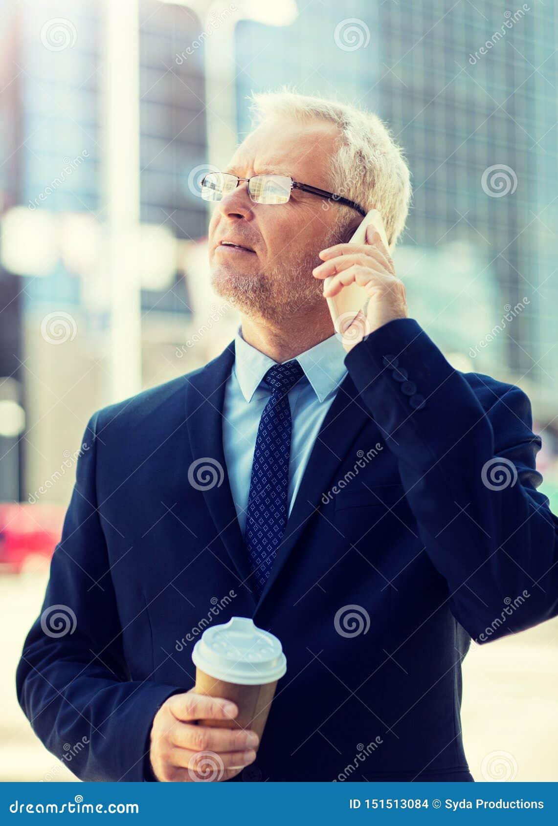 Homme d affaires sup?rieur invitant le smartphone dans la ville