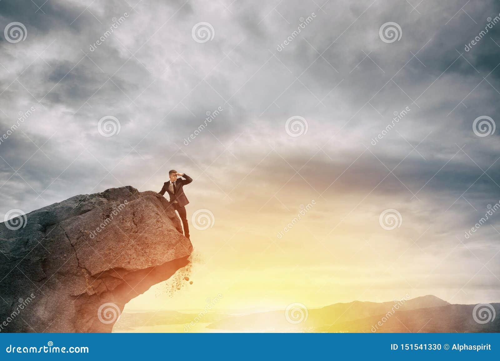 Homme d affaires sur la crête d une montagne pour trouver des affaires nouvelles
