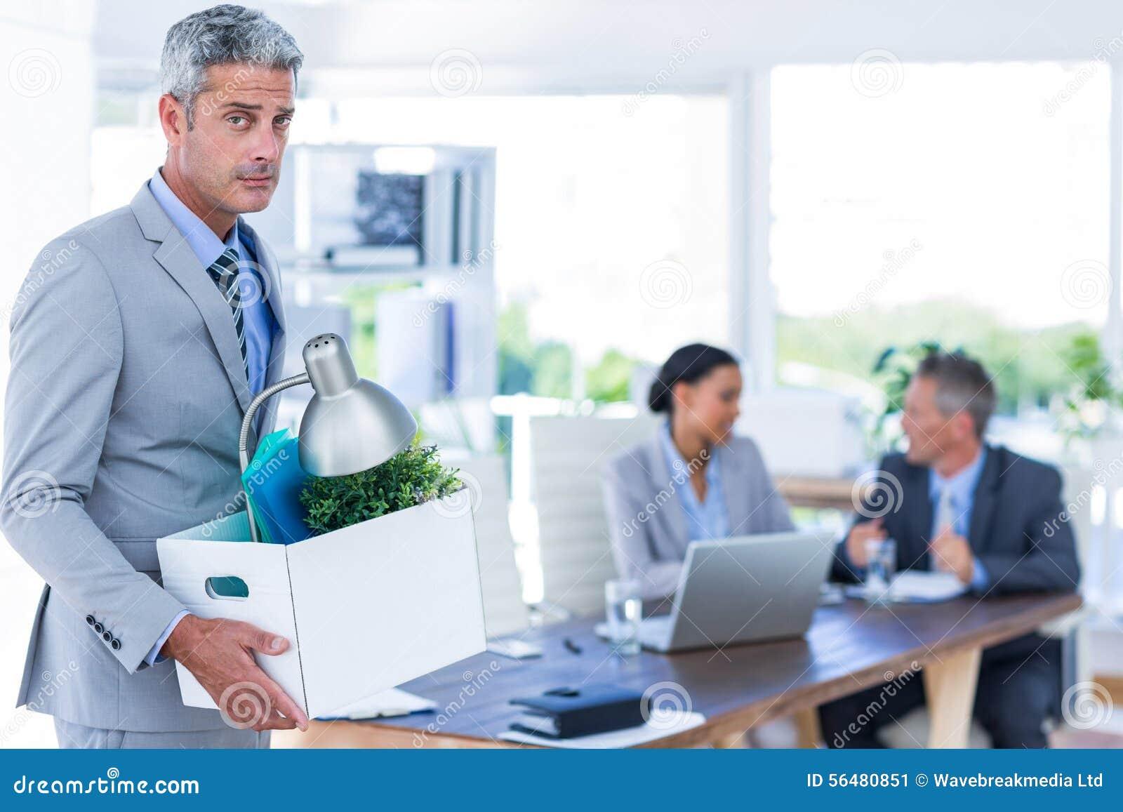 Homme d affaires tenant la boîte avec ses collègues derrière lui