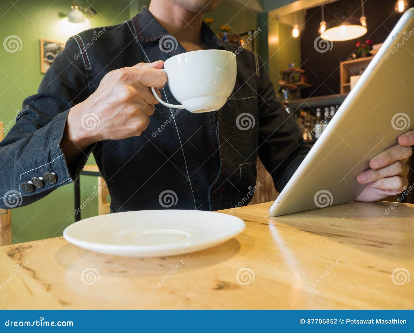 Homme d affaires tenant la tasse de café tandis qu actualités lues sur le comprimé