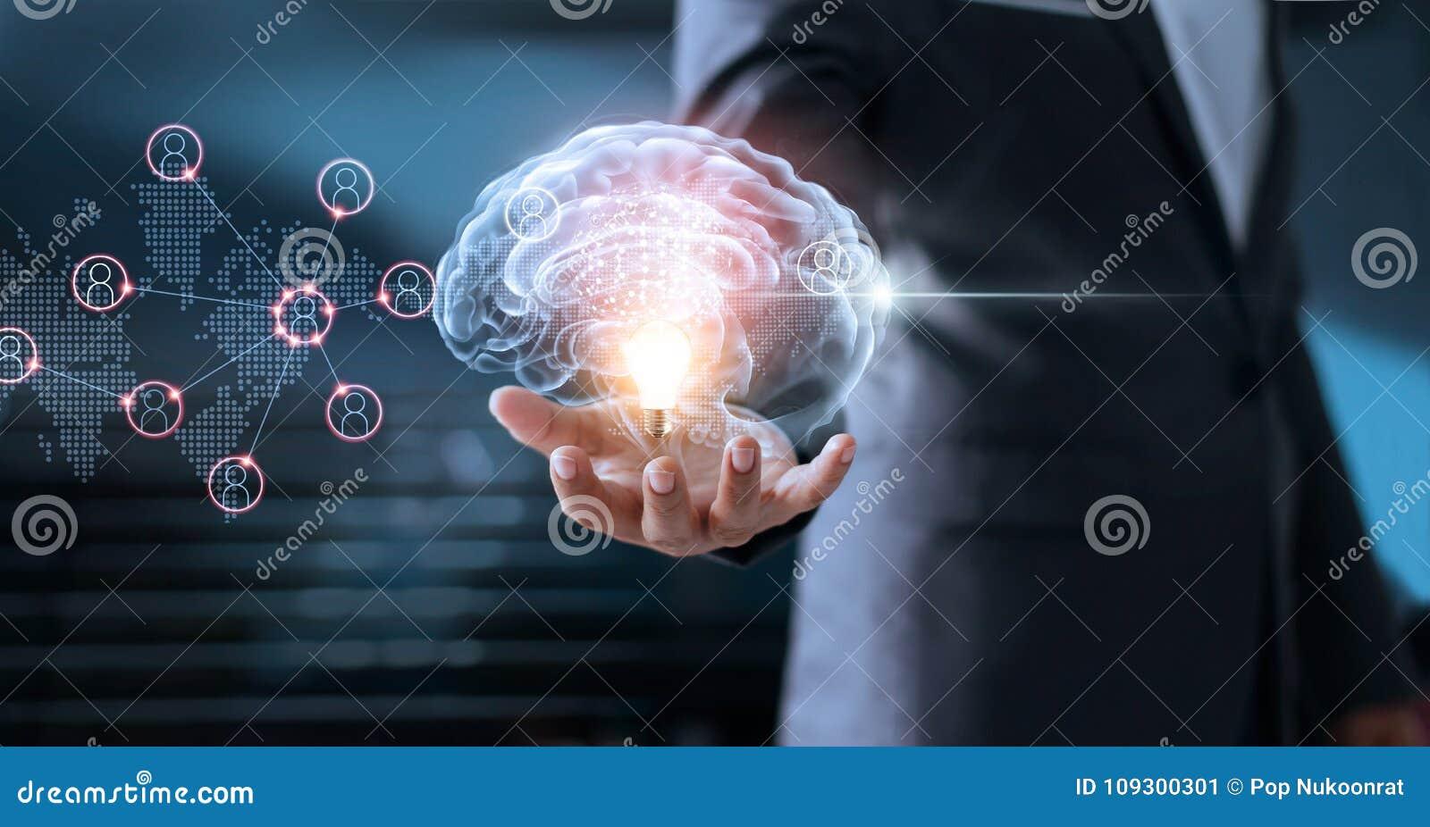Homme d affaires tenant le cerveau et l ampoule avec la mise en réseau globale