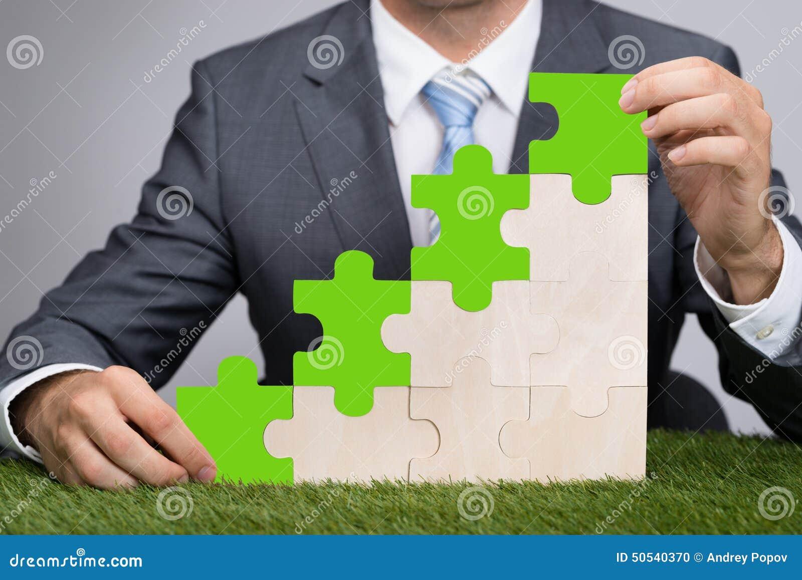 Homme d affaires tenant le graphique denteux sur l herbe