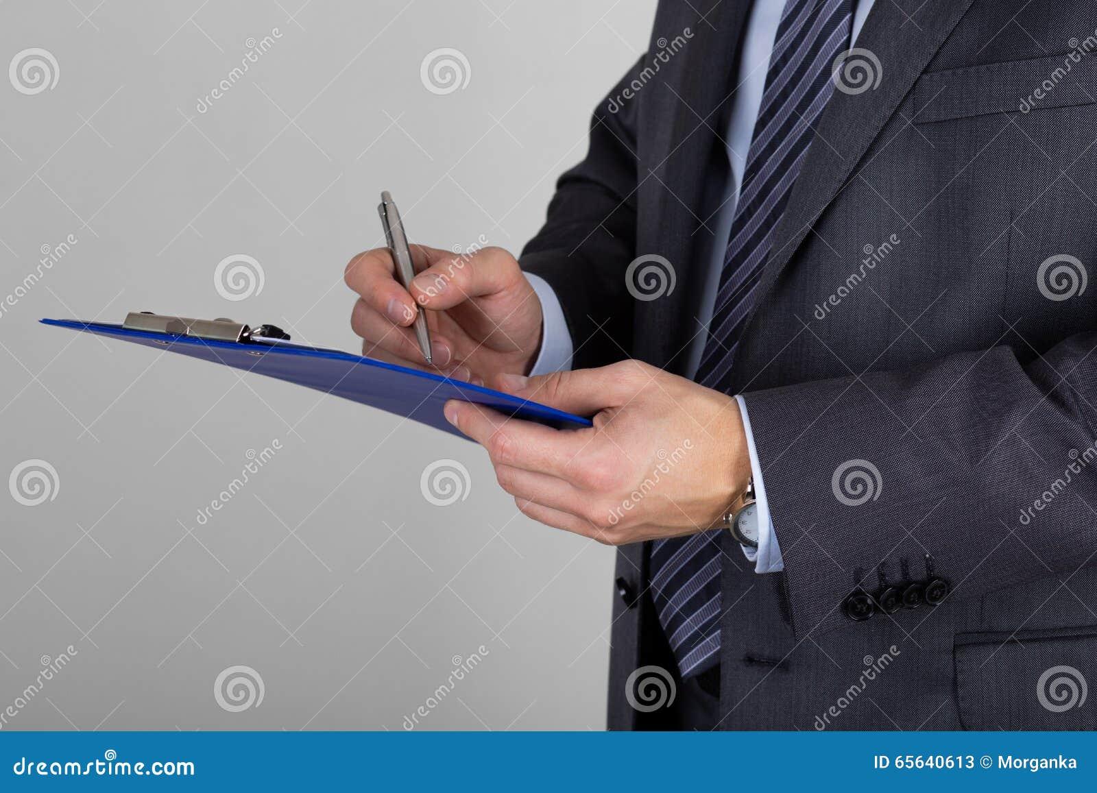 Homme d affaires tenant le presse-papiers et signant des documents