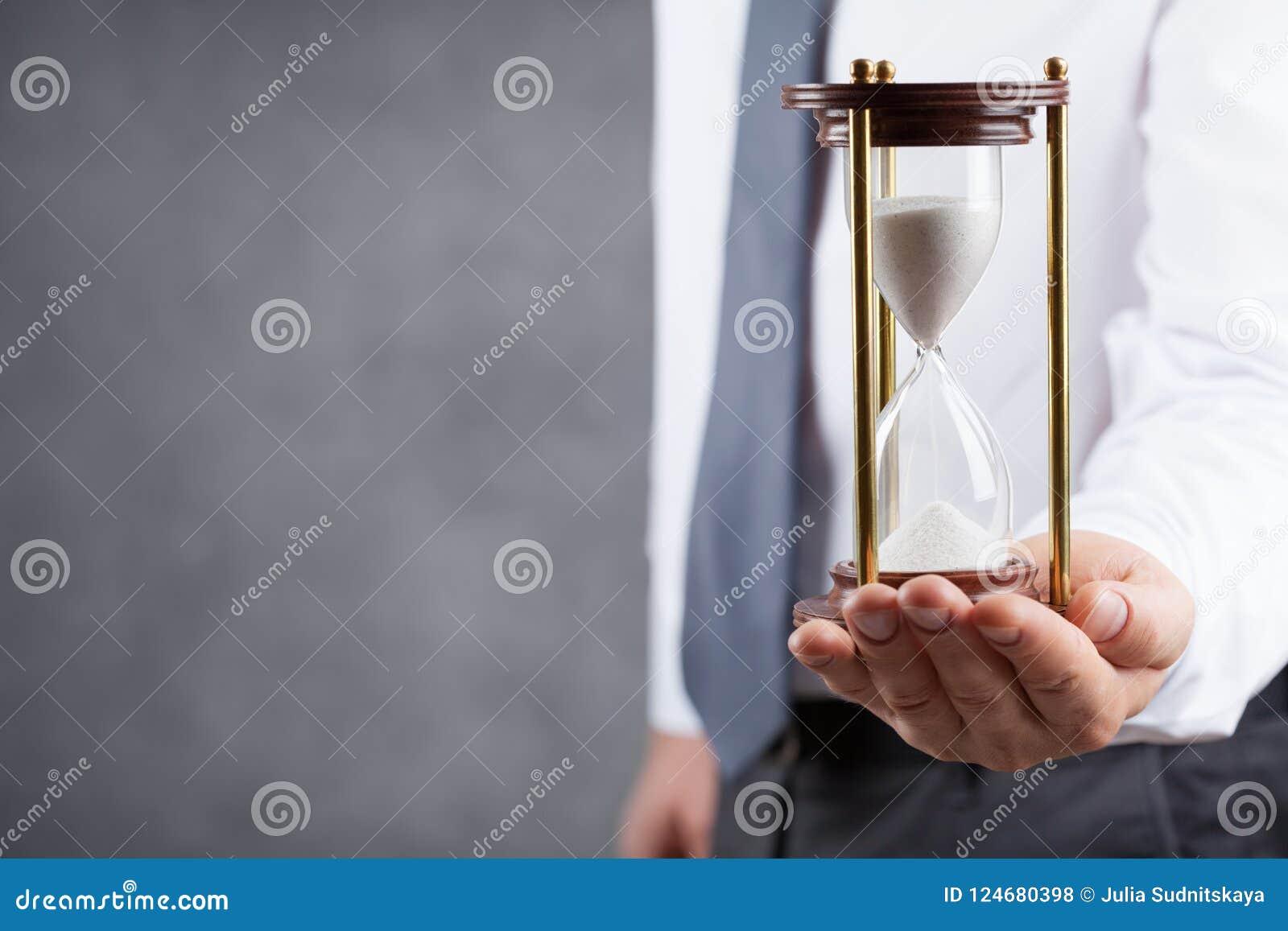 Homme d affaires tenant le sablier dans sa main Concept de gestion du temps de date-butoir et