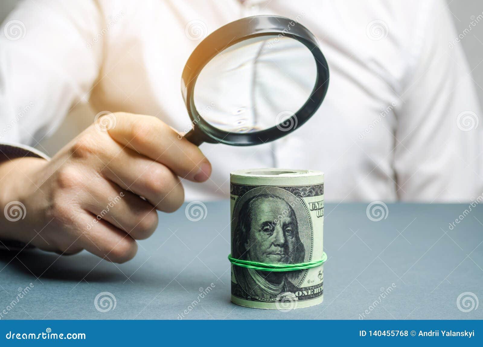 Homme d affaires tenant une loupe au-dessus des dollars Analyse du revenu et des bénéfices Le concept de trouver des sources de