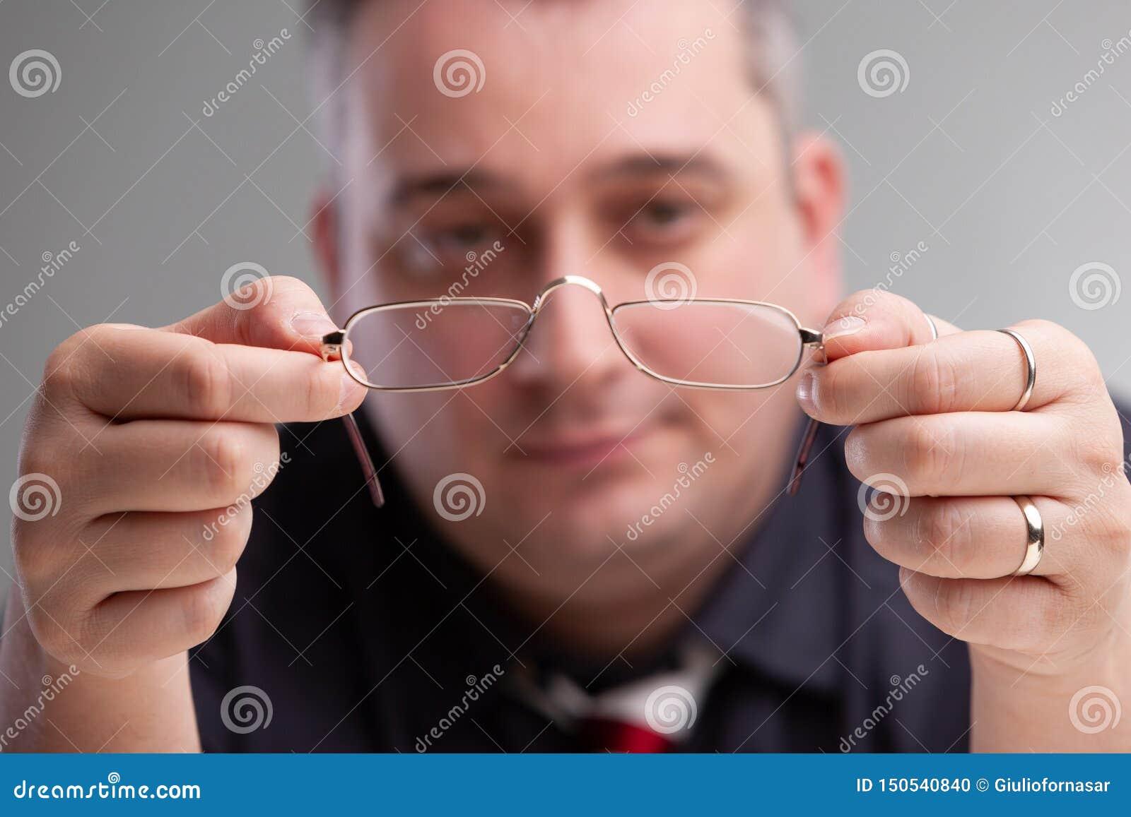 Homme d affaires tenant une paire de lunettes