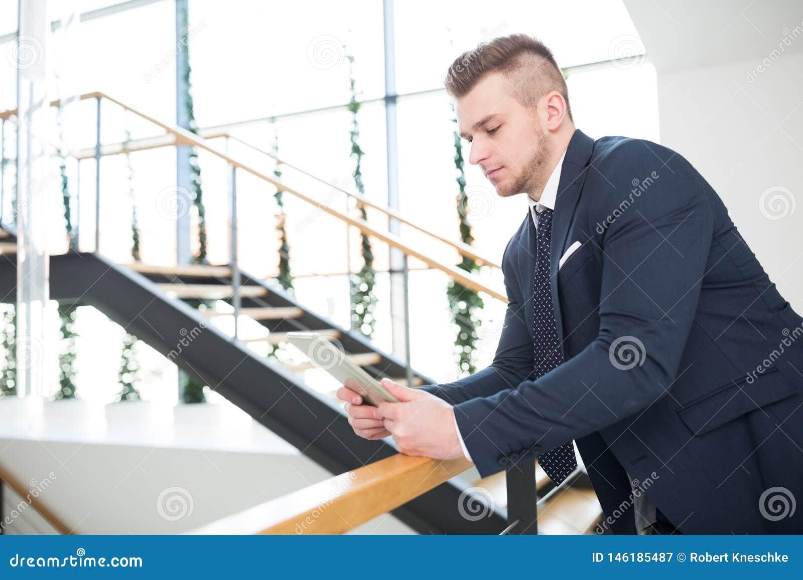 Homme d affaires Using Digital Tablet tout en se penchant sur la balustrade
