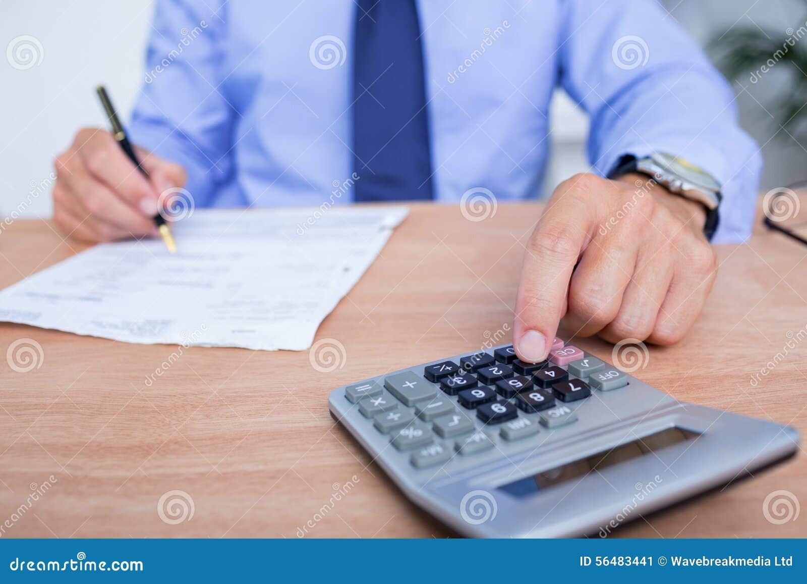 Homme d affaires utilisant la calculatrice tout en écrivant