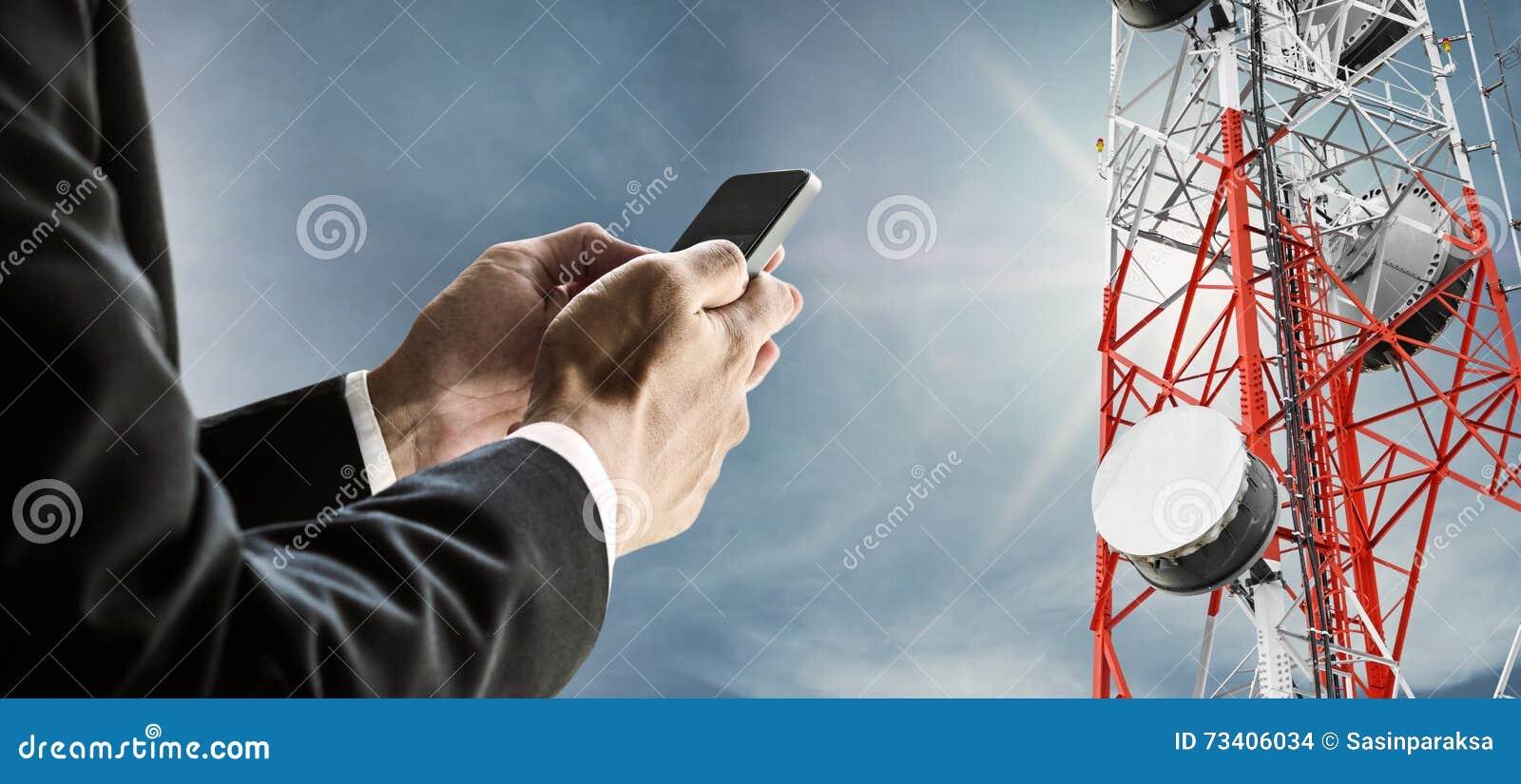 Homme d affaires utilisant le téléphone portable, avec le réseau de télécom d antenne parabolique sur la tour de télécommunicatio