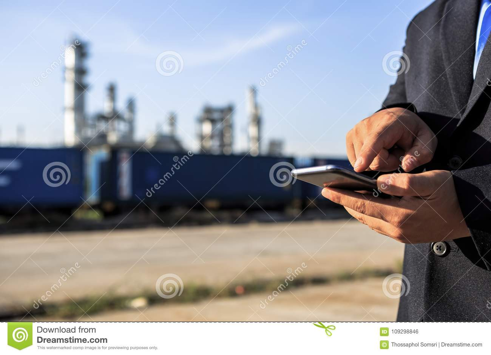 Homme d affaires vérifiant autour de l usine de raffinerie de pétrole avec le ciel clair