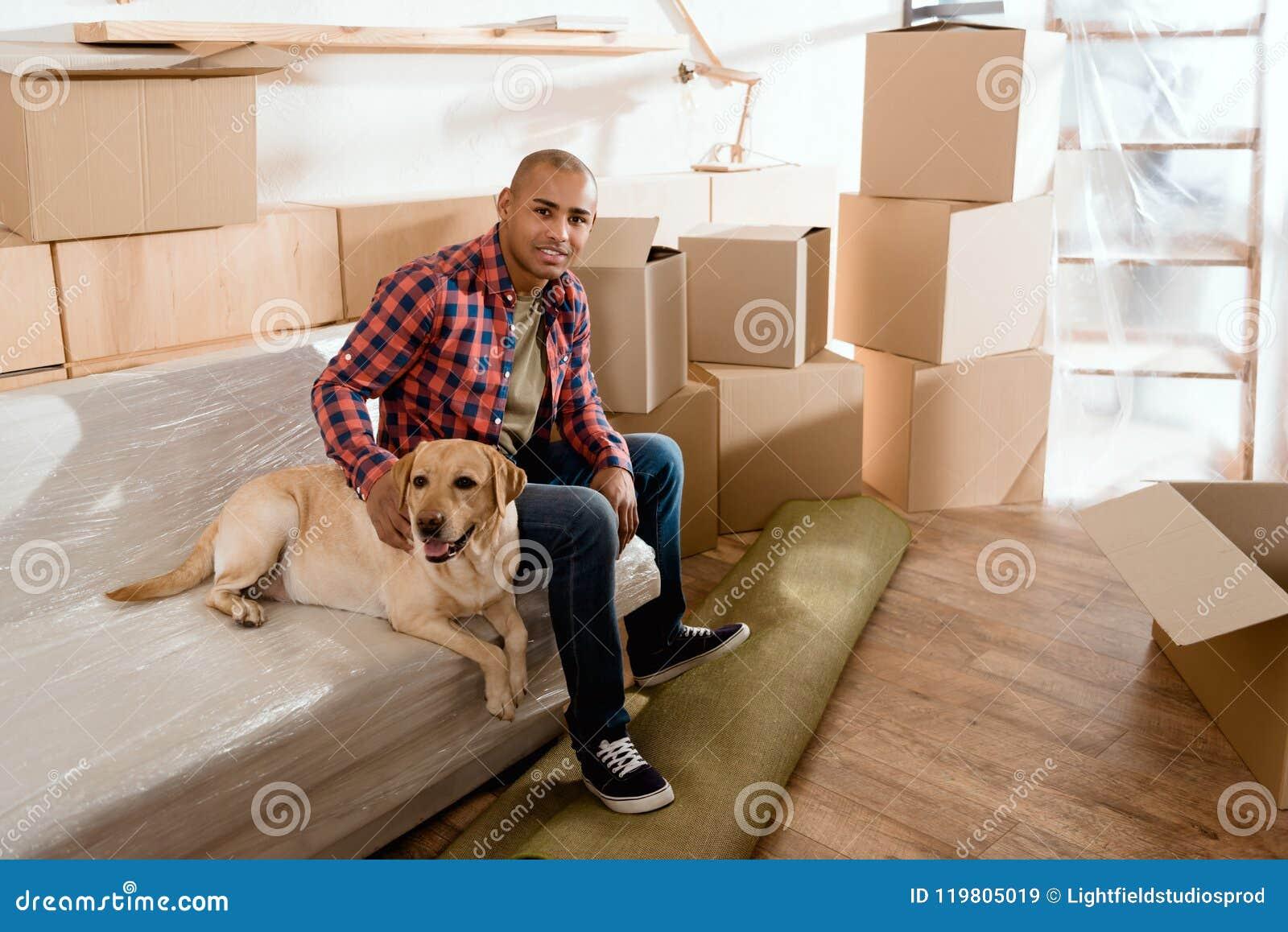 Homme d afro-américain avec le chien de Labrador en nouvel appartement