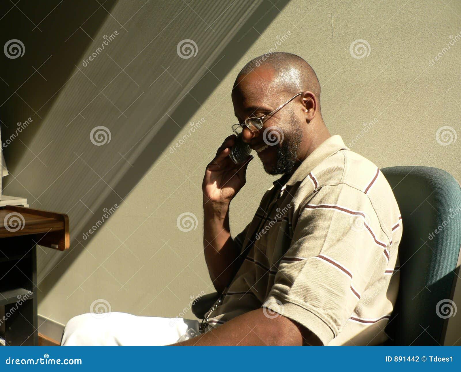 Homme d Afro-américain sur le portable dans les ombres
