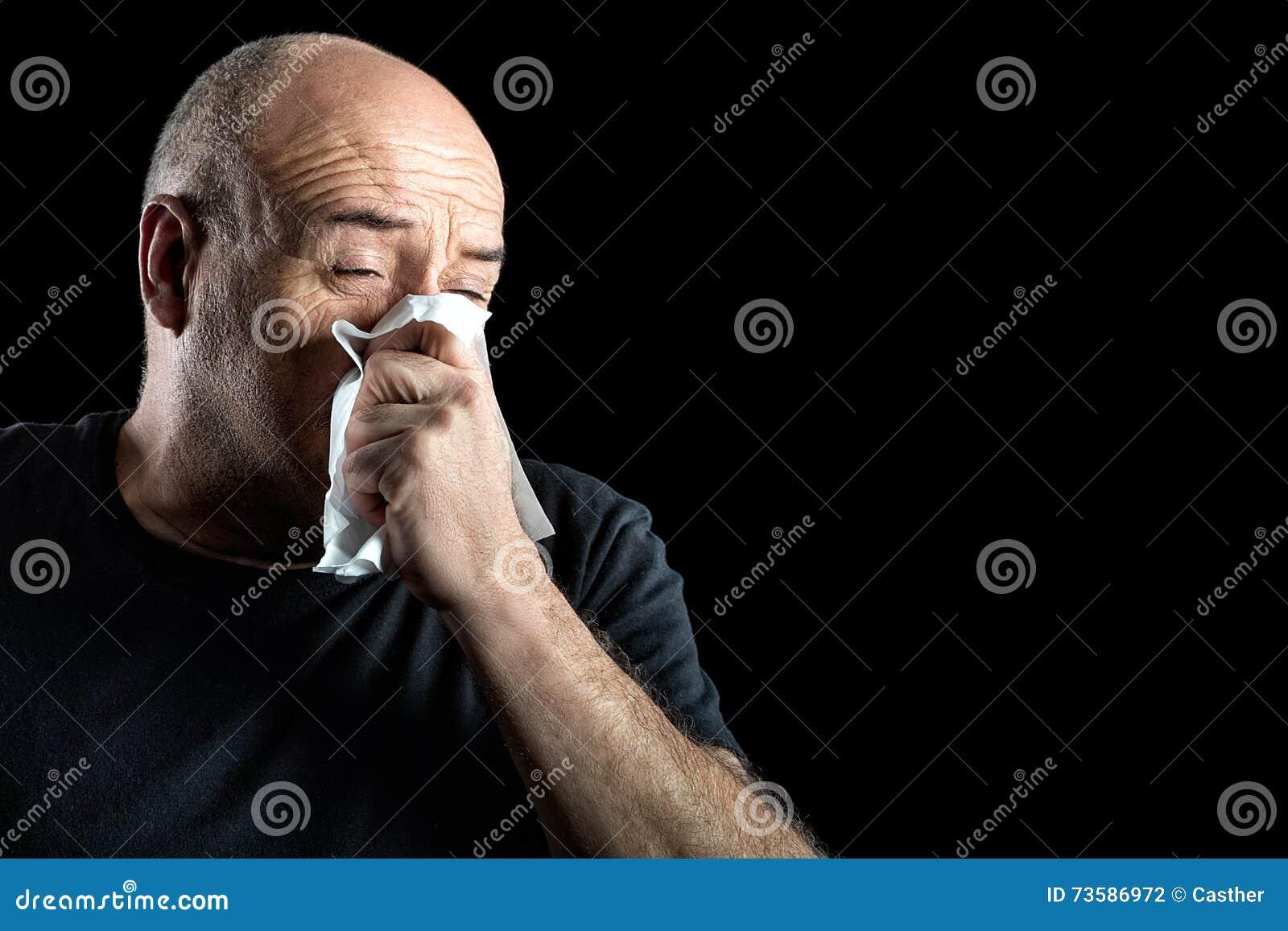 Homme d une cinquantaine d années avec la grippe soufflant son nez
