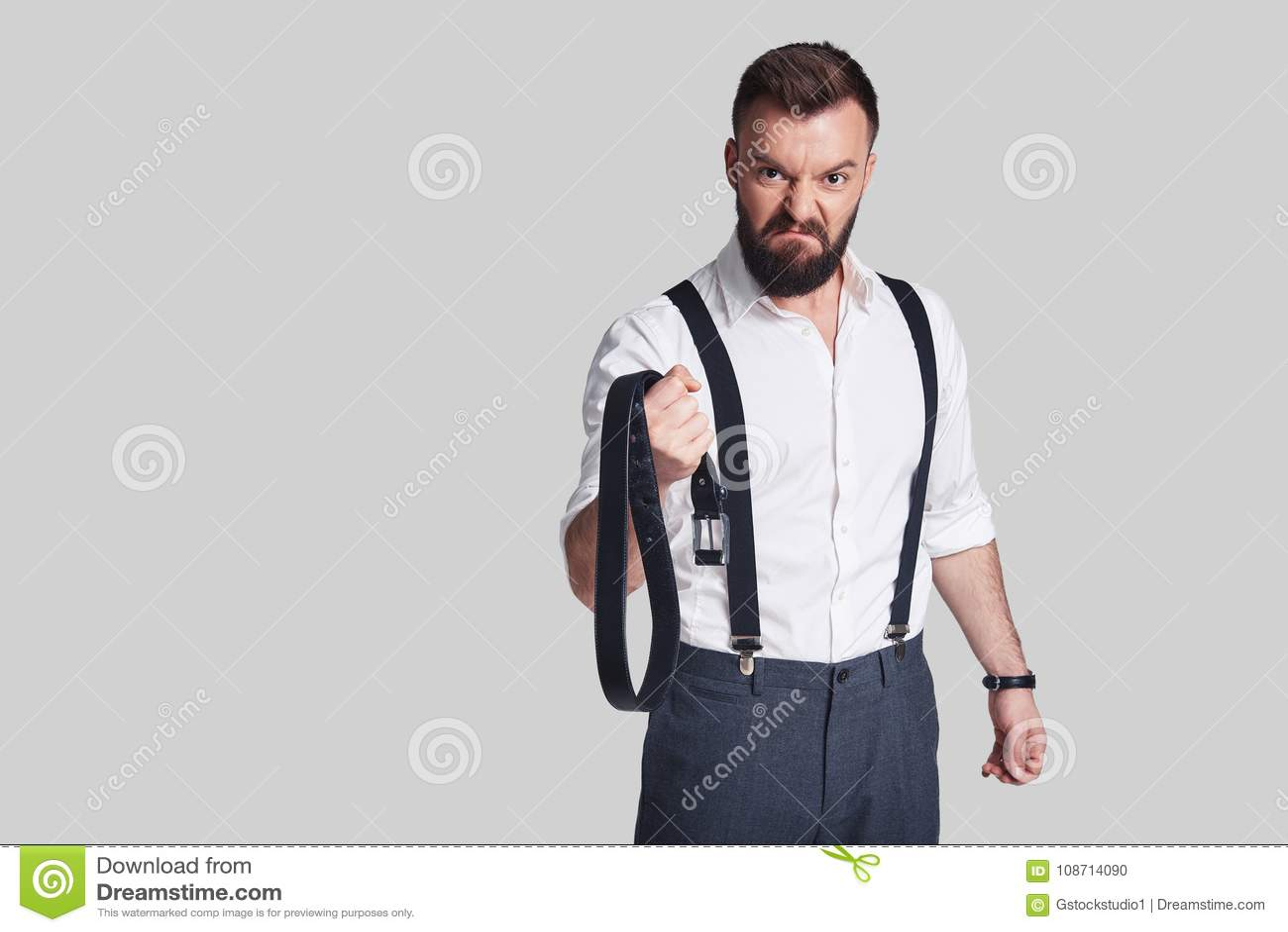 3c2171faed3 Homme dangereux Jeune homme fâché dans le formalwear portant une ceinture et