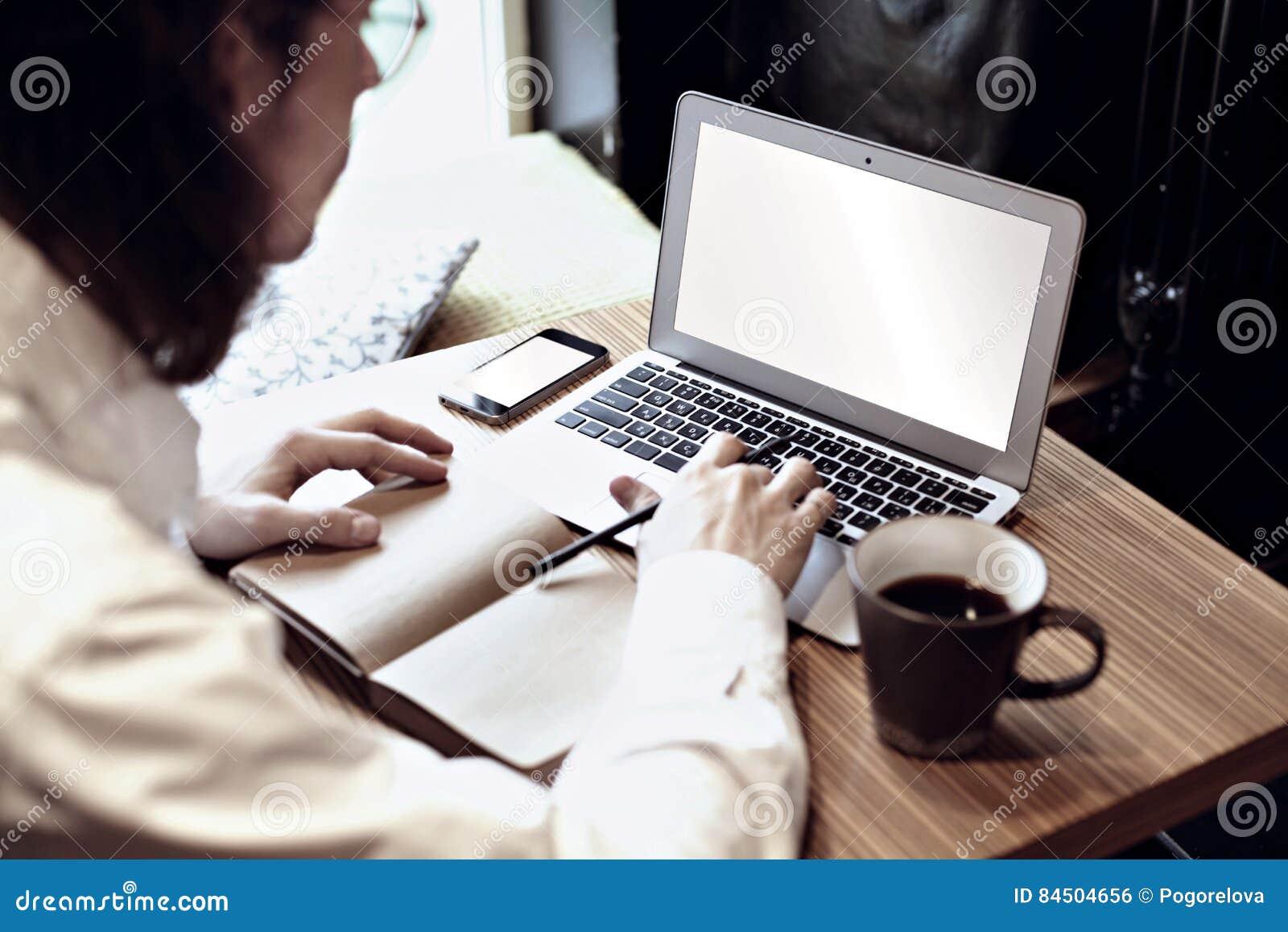 Homme dans la chemise blanche travaillant à l ordinateur portable et au café potable dans un café ou un Co-travail Foyer au clavi