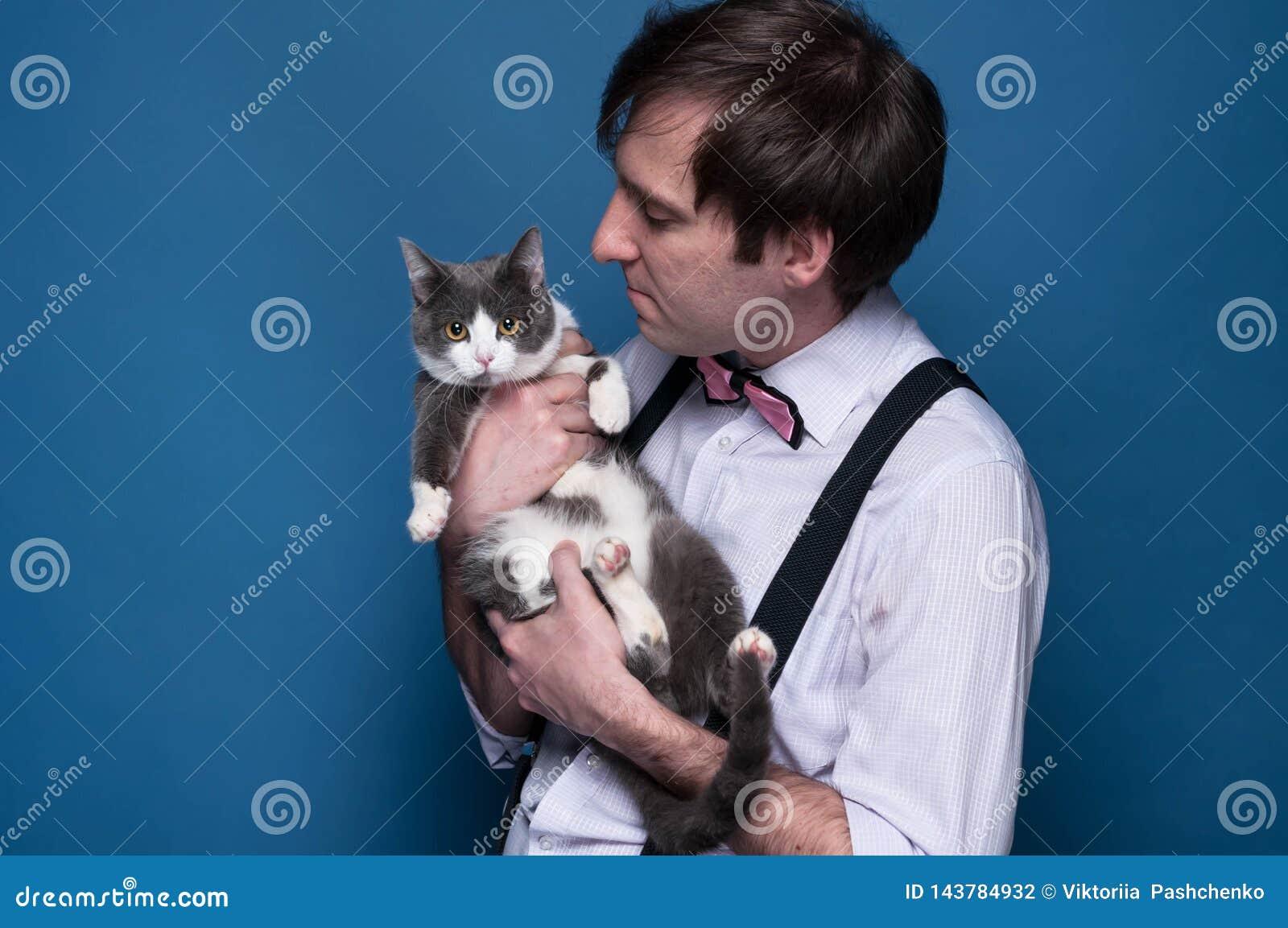 Homme dans la chemise, la bretelle et le noeud papillon rose se tenant et regardant au chat gris mignon avec les pattes blanches