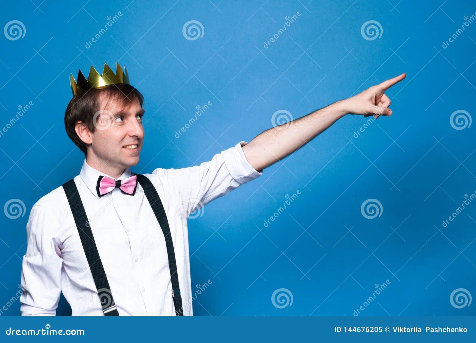 Homme dans la chemise, la bretelle, le noeud papillon et la couronne d or, souriant, regardant loin et ponting avec le doigt dans