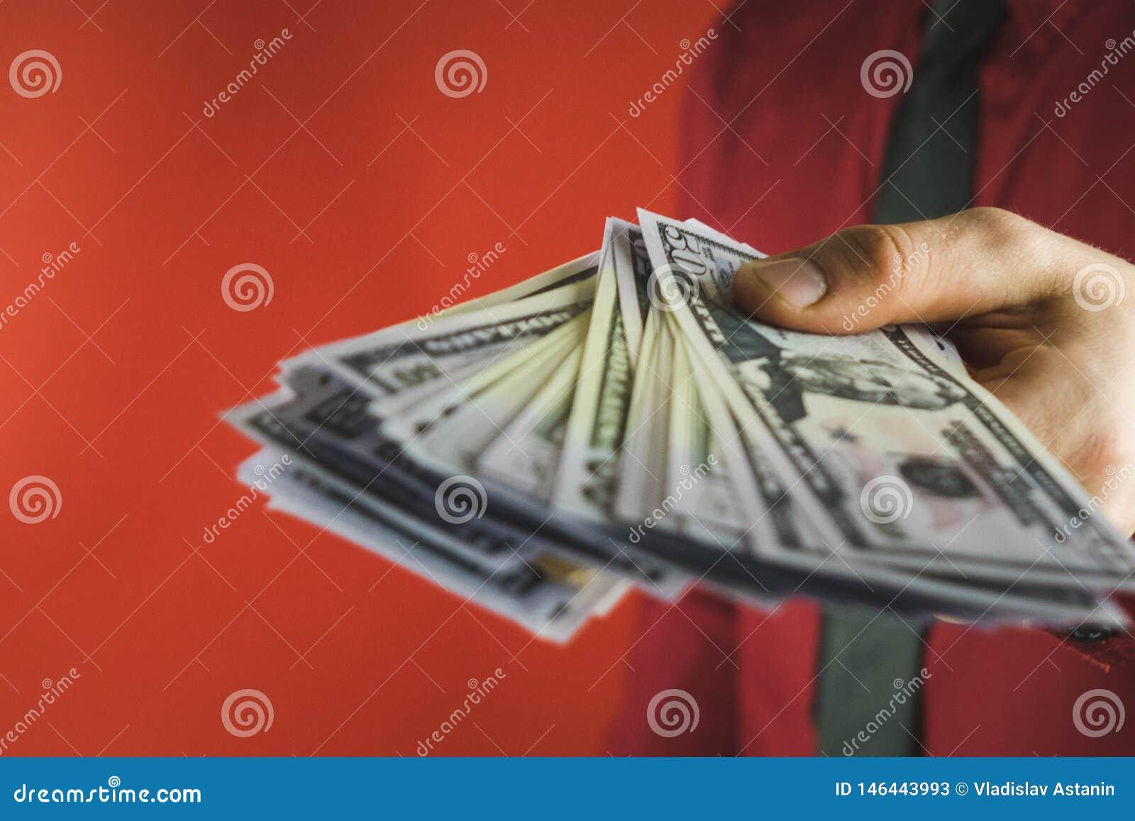 Homme dans la chemise rouge avec une exploitation un paquet de factures dans sa main sur un fond rouge