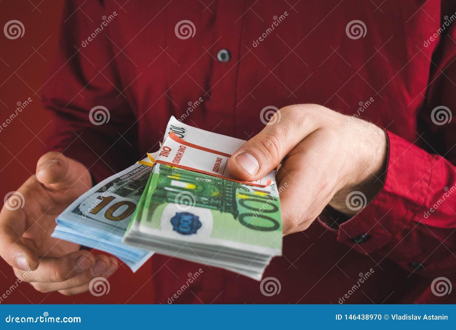 Homme dans la chemise rouge tenant des paquets d argent sur le fond rouge