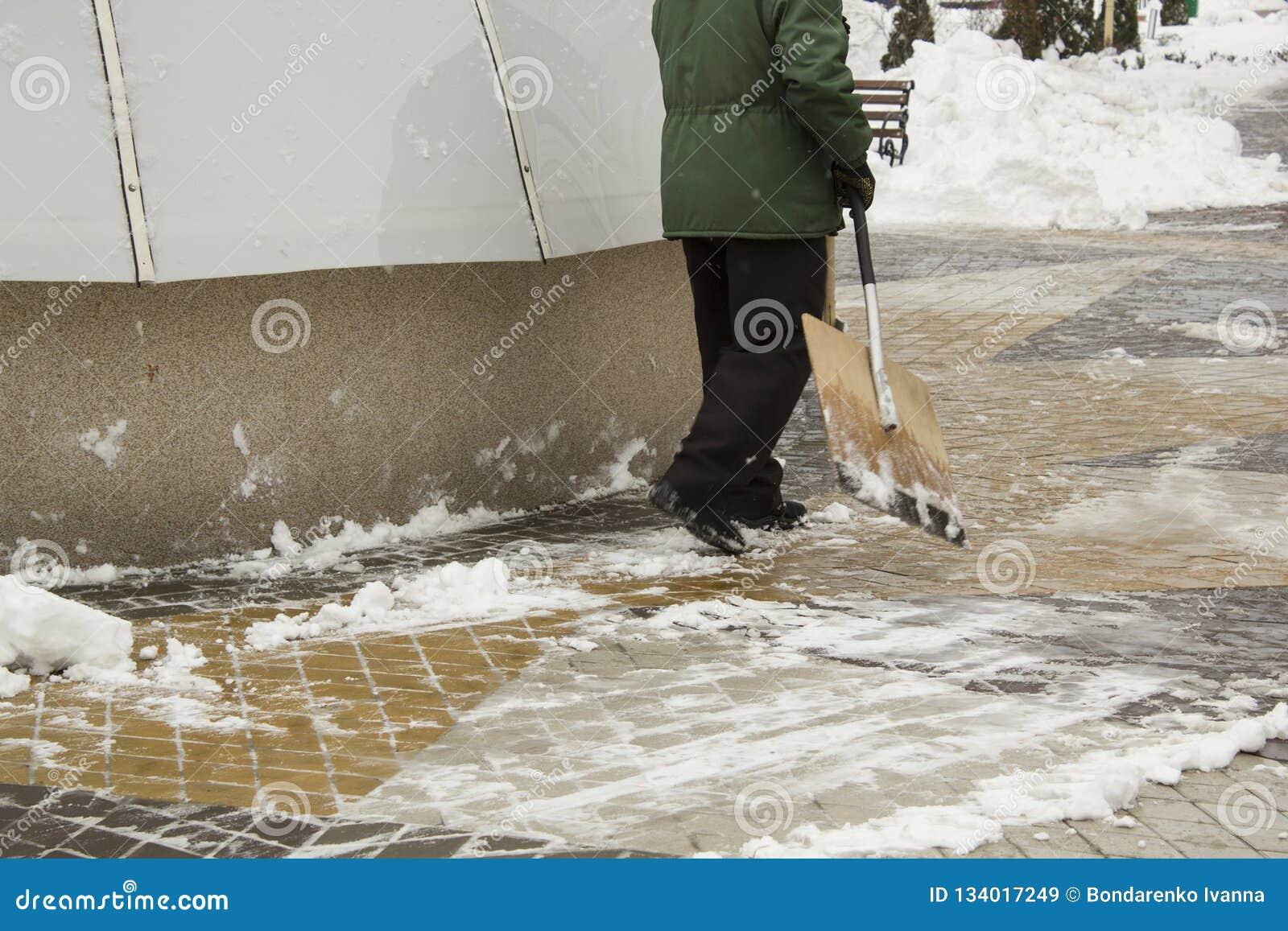 Homme dans la neige de nettoyage uniforme avec une pelle