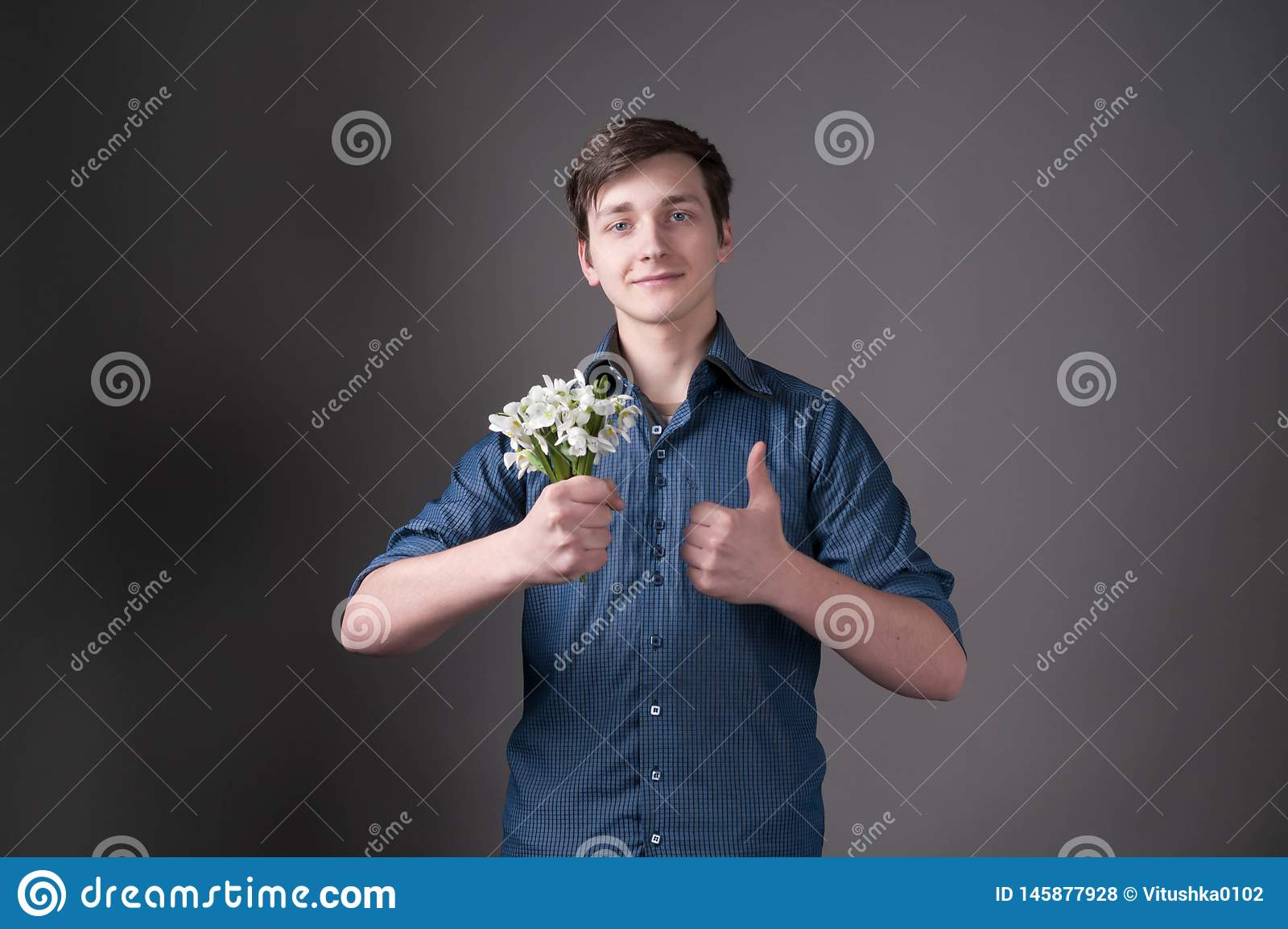 Homme dans le bouquet bleu de participation de chemise avec des perce-neige, regardant la caméra et la maniant maladroitement sur