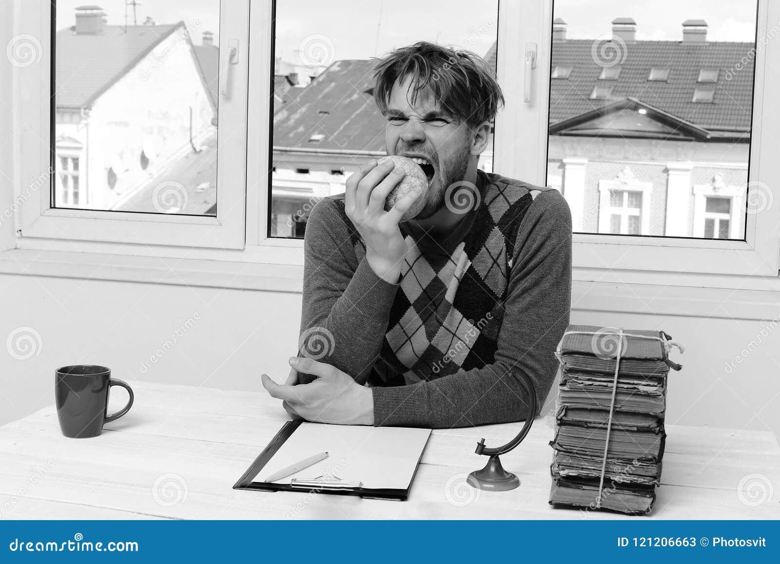Homme dans le chandail se reposant au bureau avec la pile de livres
