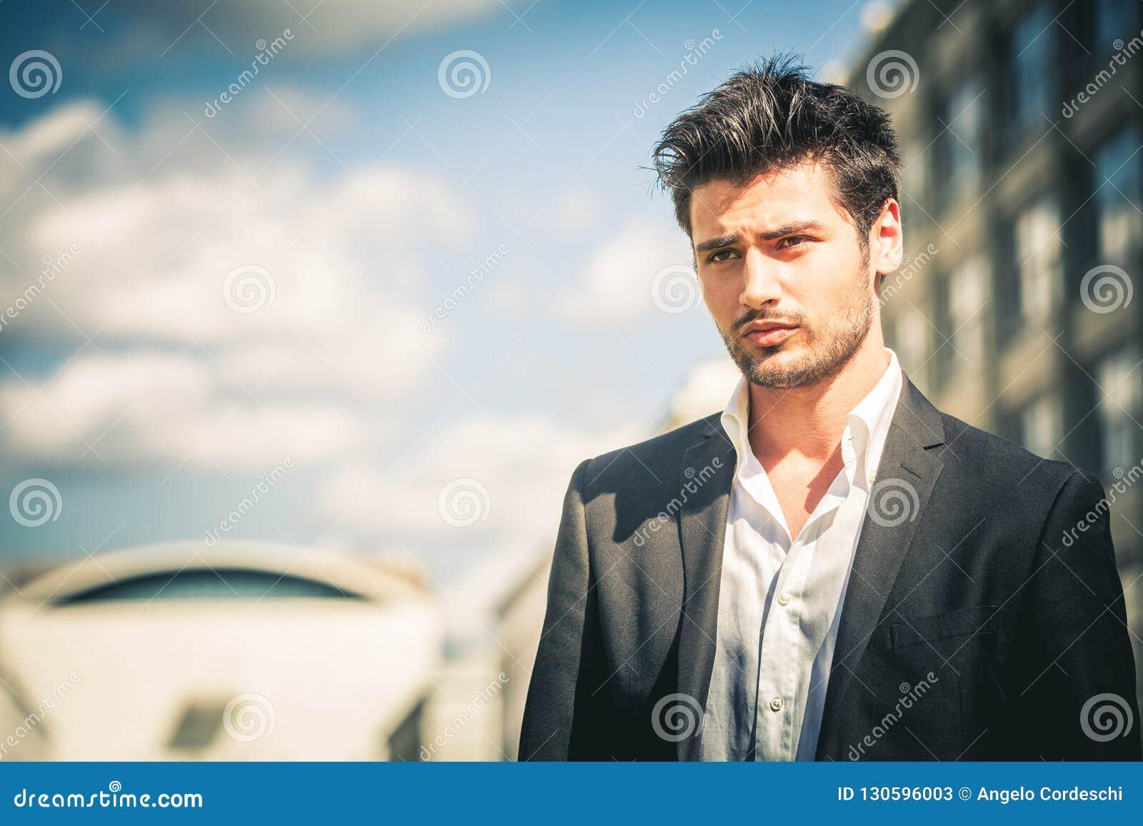 Homme dans le costume et le regard blanc de chemise Avec les cheveux et la  barbe à la mode Dehors sur la rue dans la ville Ciel et bâtiments à  l arrière- ... 52e3d9ac9dd