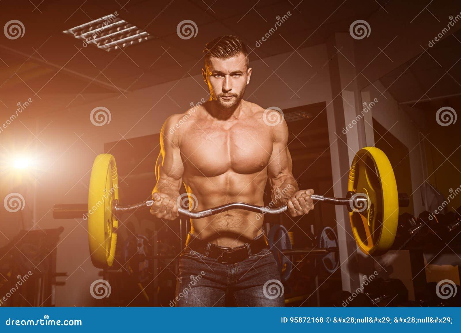 Homme dans le gymnase Type musculaire de bodybuilder faisant des exercices avec le barbell Personne intense Folâtre le fond Jeune