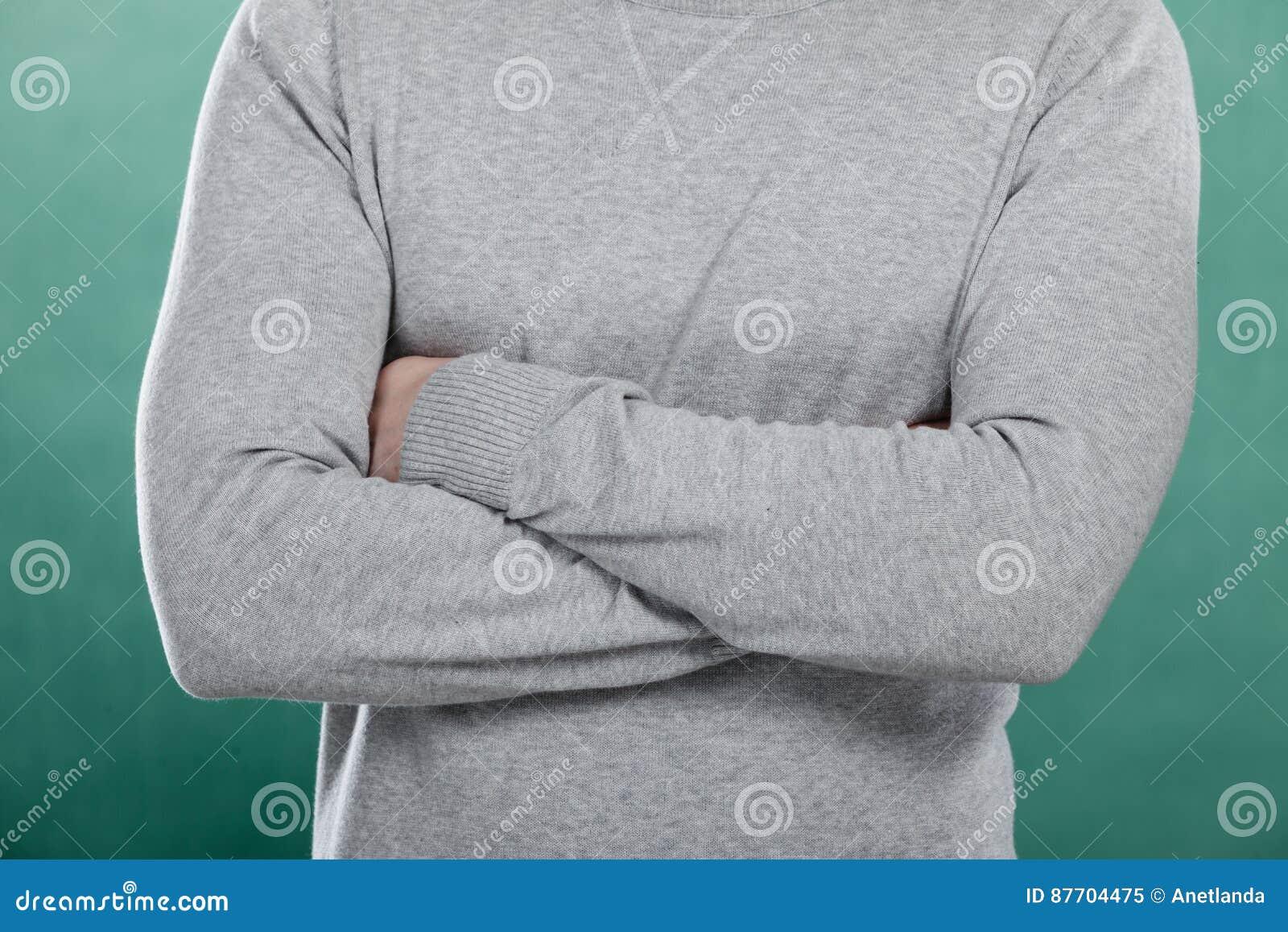 Homme dans le pullover gris avec les bras croisés