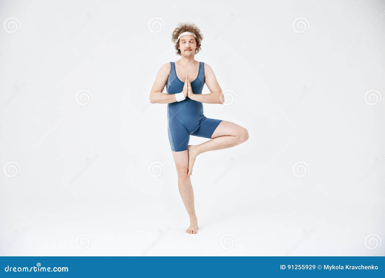 Homme dans le yoga de pratique d habillement de sport de style ancien Vrikshasana avec des yeux fermés