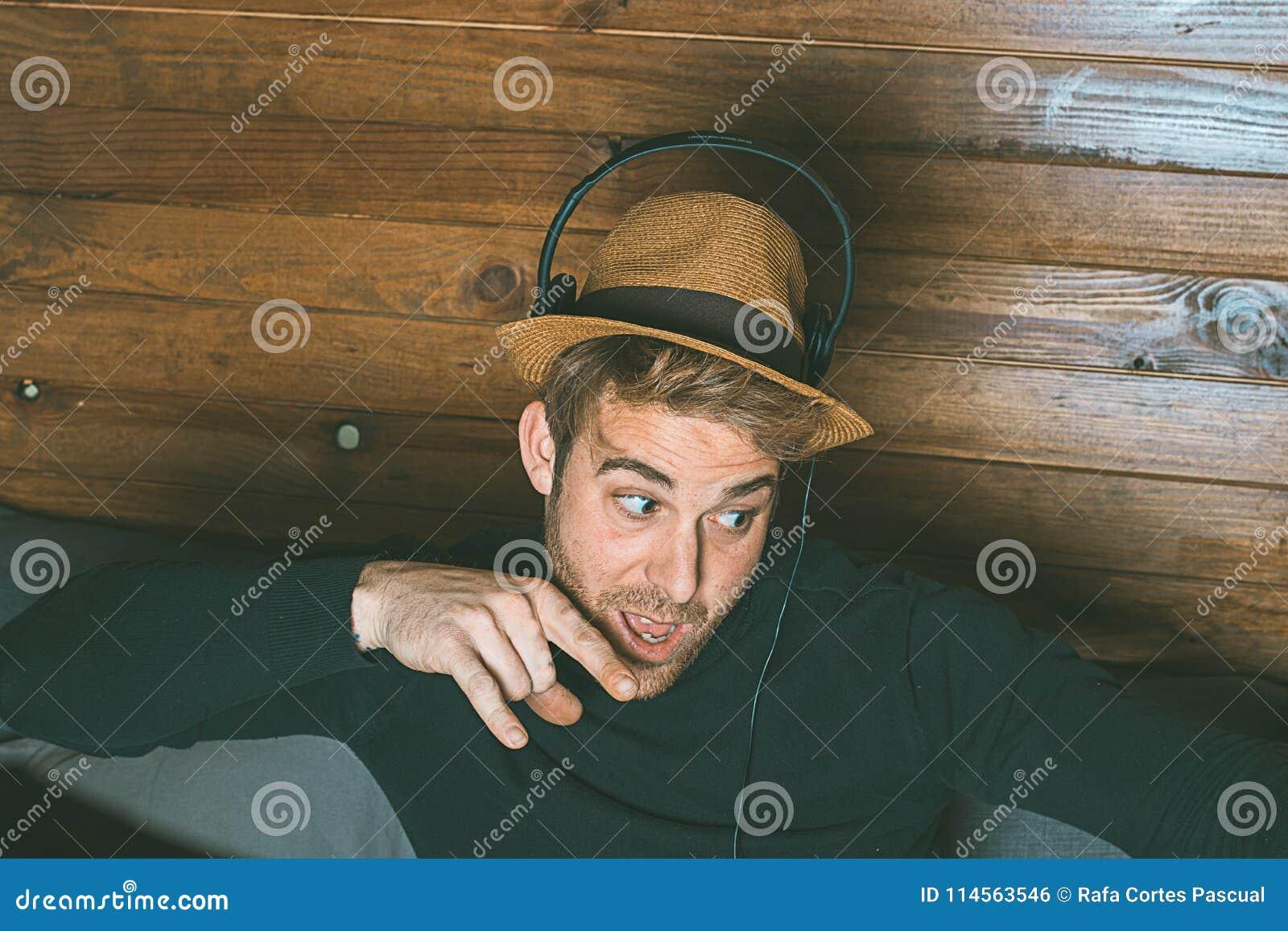 Homme dans un chapeau et des écouteurs faisant les visages drôles