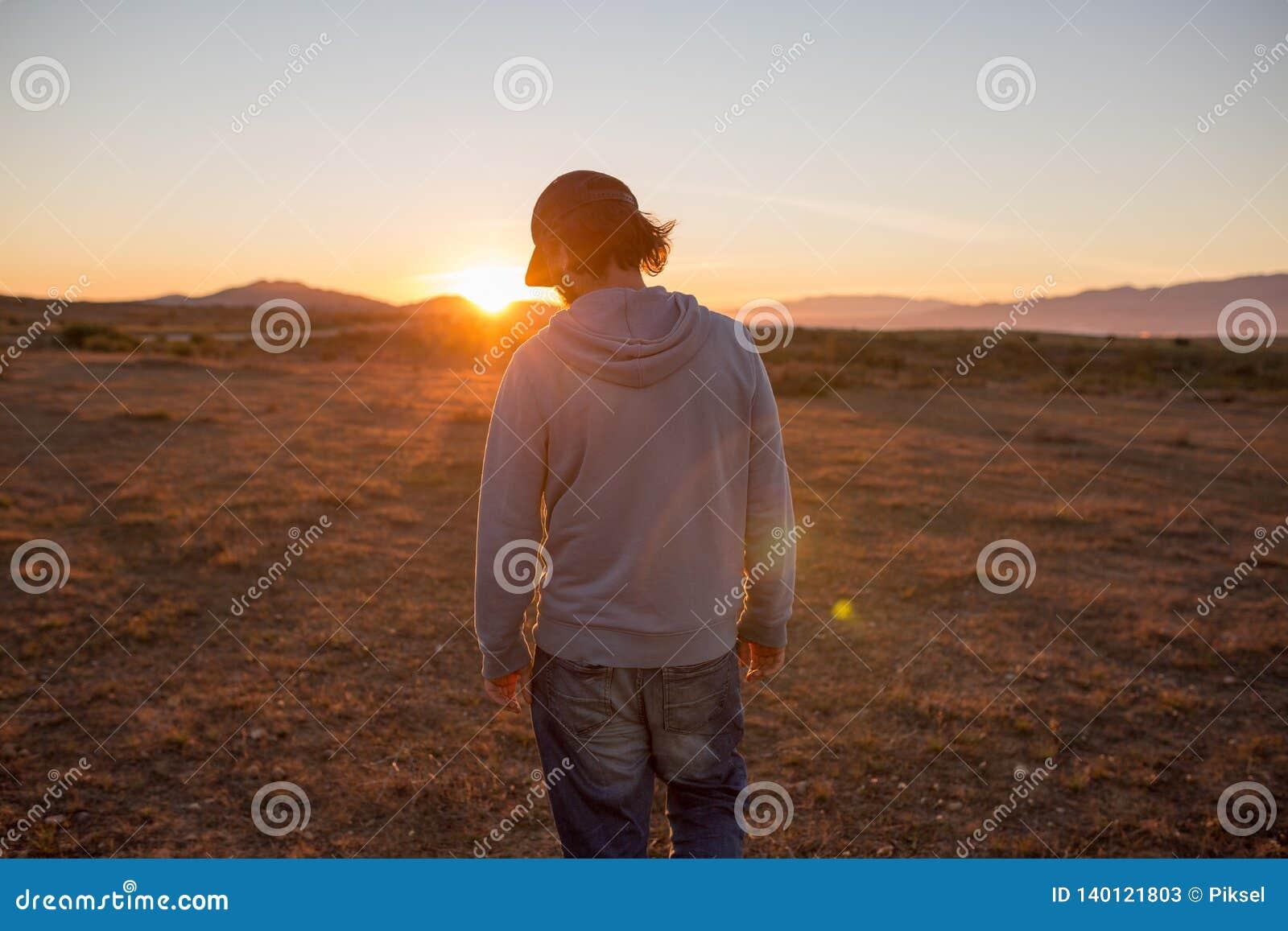 Homme dans un paysage immaculé pendant un beau coucher du soleil de flambage