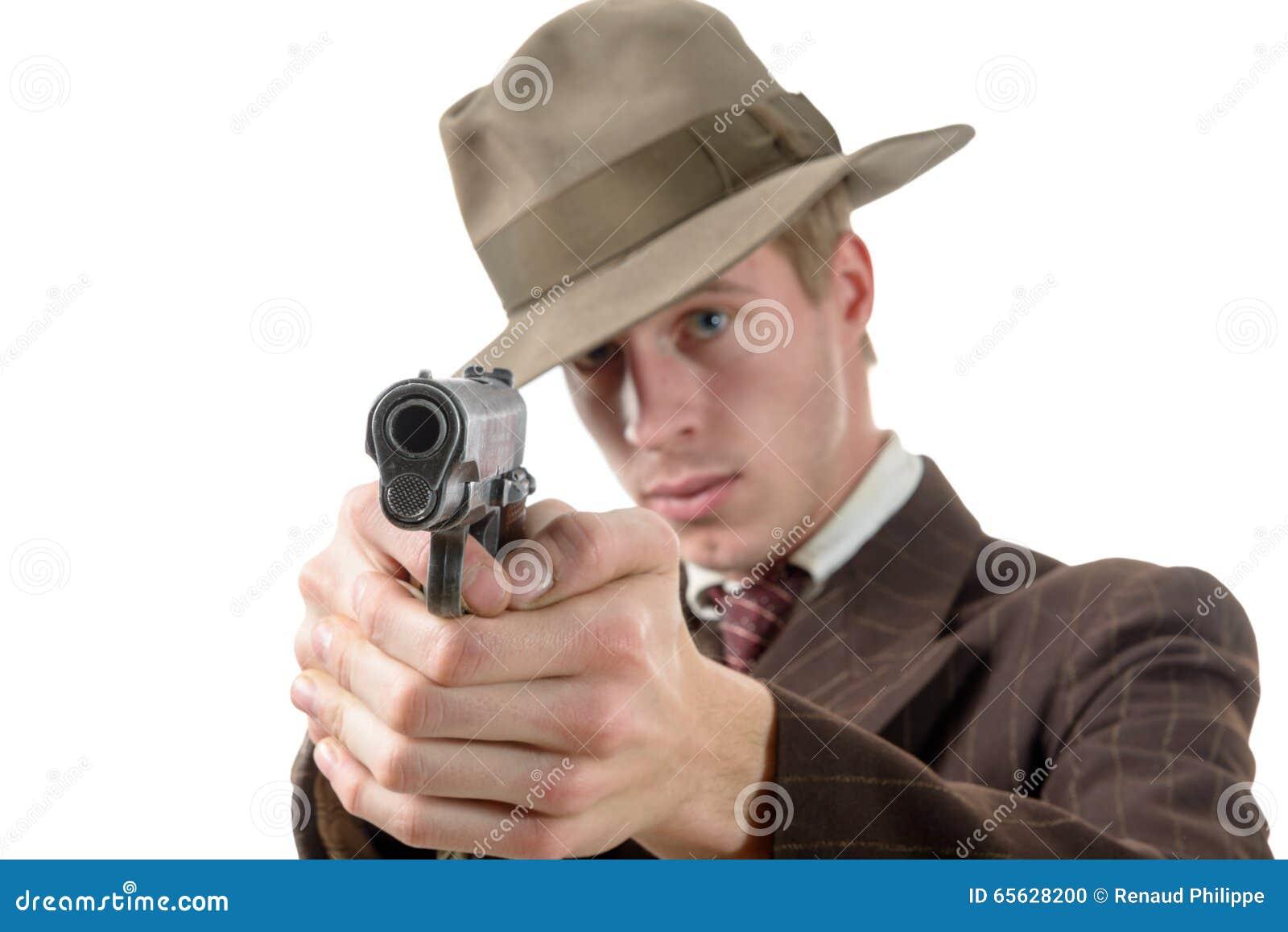 Homme dans un vintage de costume, but avec une arme à feu, sur le blanc