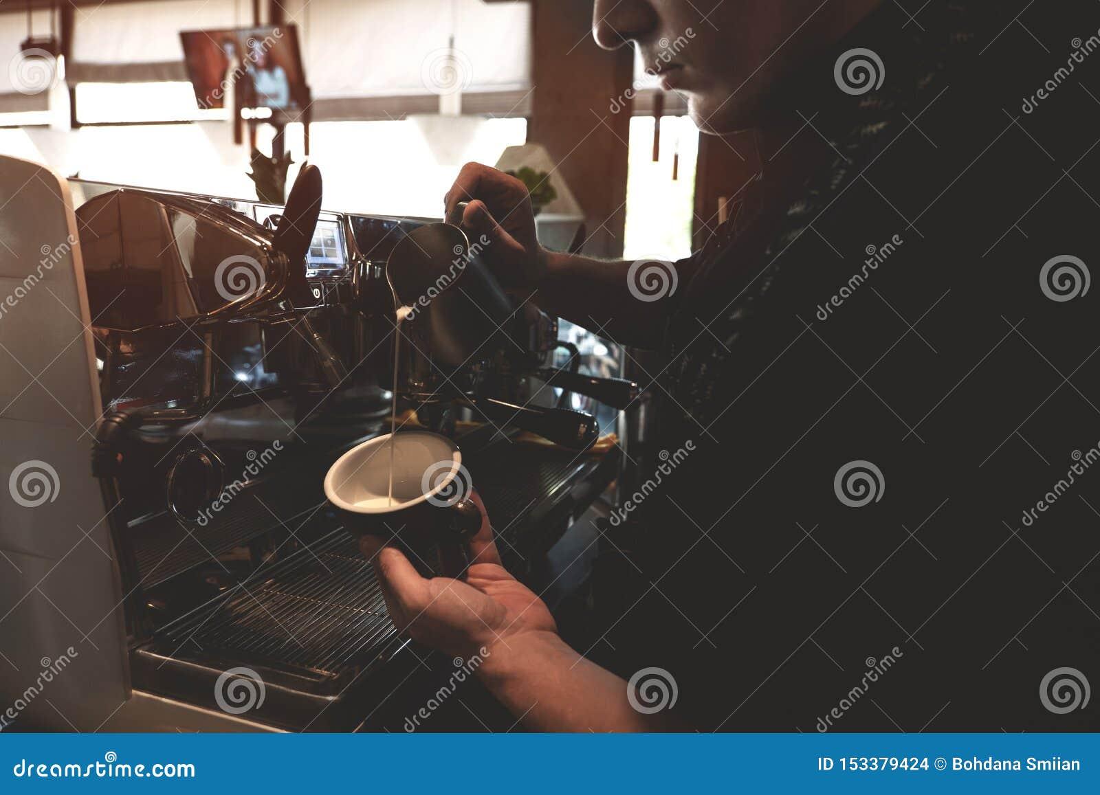 Homme de barman versant le lait fouetté de mousser le broc dans la tasse avec la position de boissons de café près du café profes