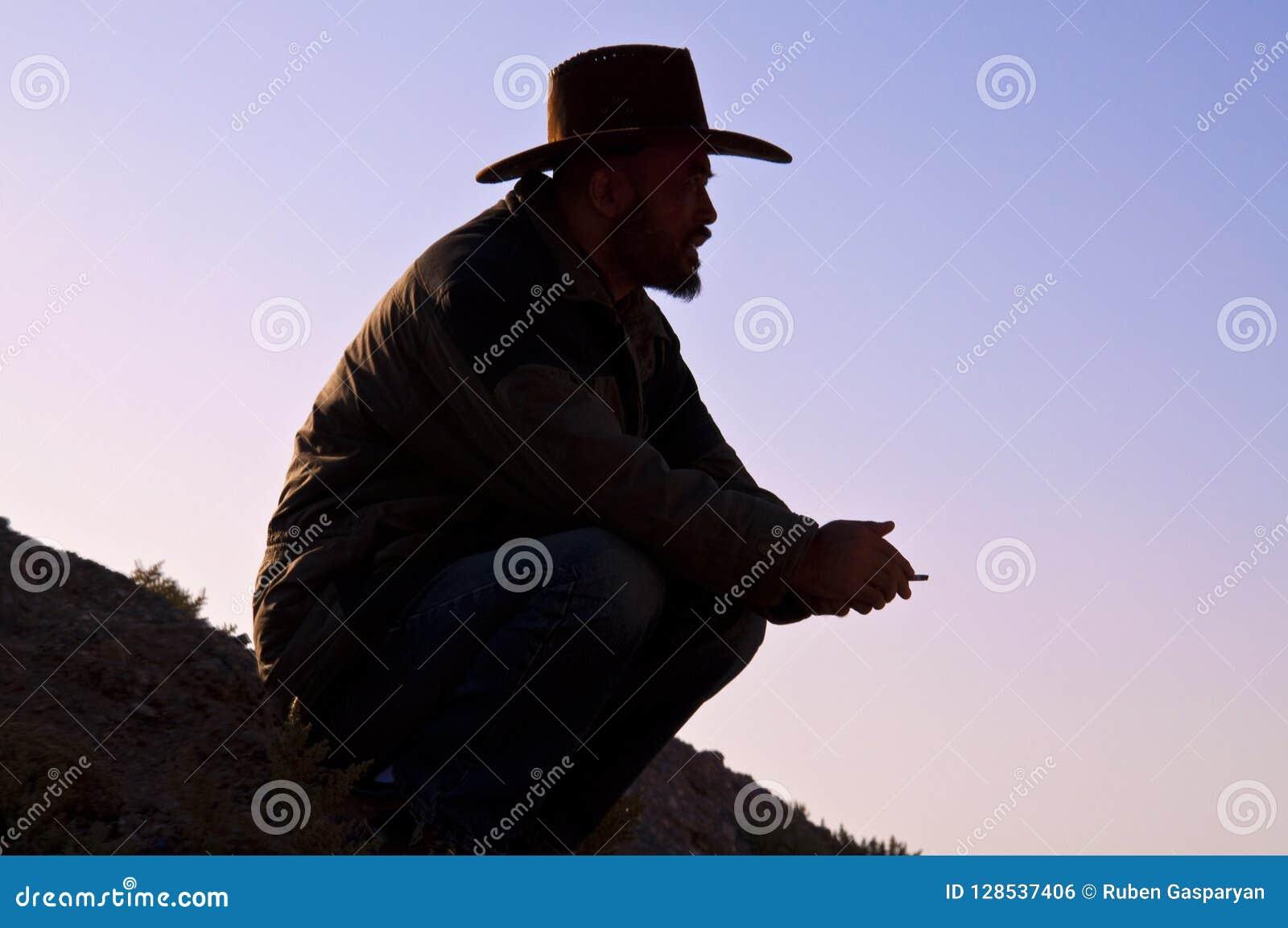 Homme de cowboy s asseyant au lever de soleil