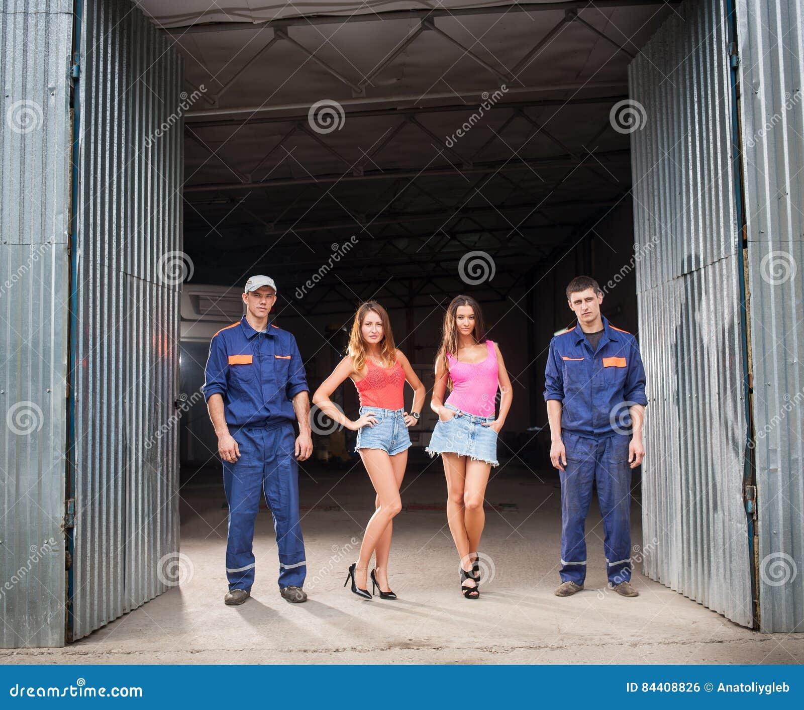 Homme de deux mécaniciens automobiles et deux belles filles sexy