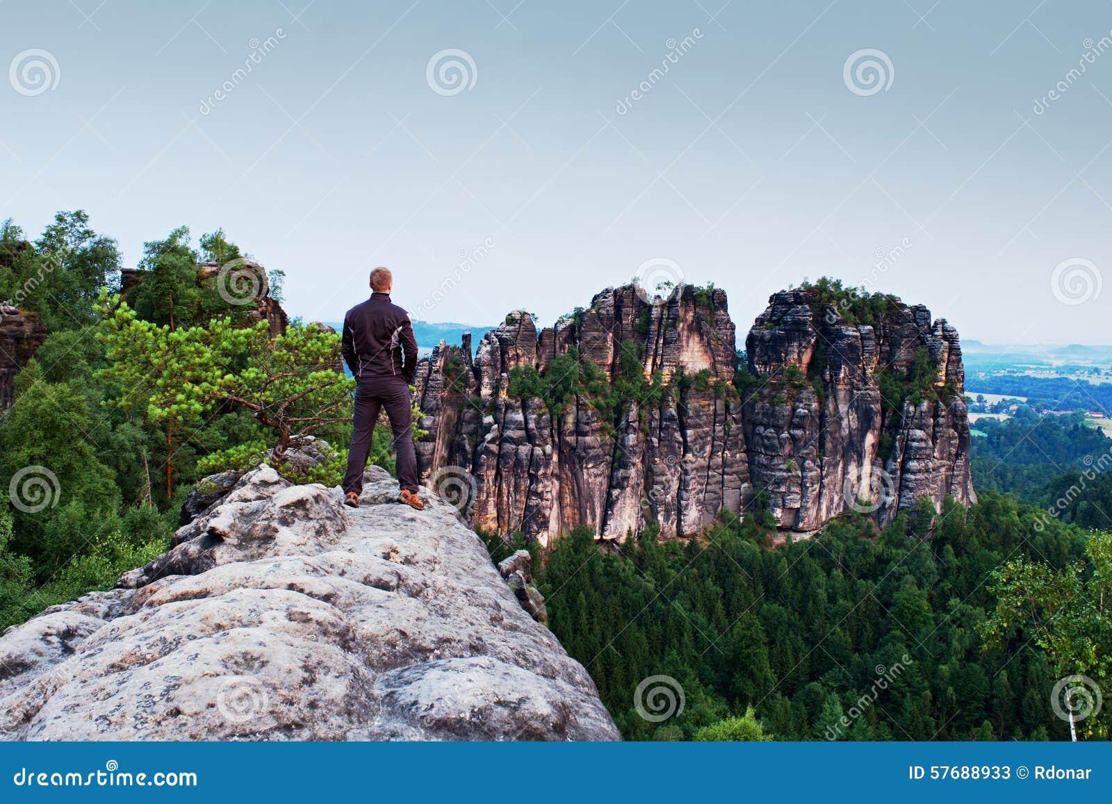 Homme de grimpeur dans le noir sur la fortes falaise et montre aux montagnes  Silhouette foncée 23ede51b708